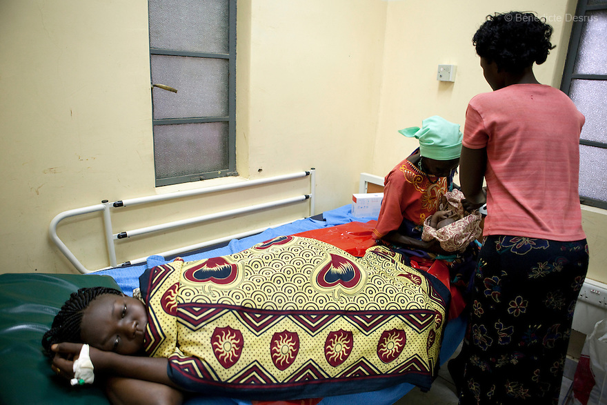 July 6, 2011 - Juba, Republic of South Sudan - Rose Kadi, a 26 year old South Sudanese woman, lies in her bed after giving birth to her newborn baby while her mother and sister look on at Juba Teaching Hospital, South Sudan's oldest, and by far the largest and best-equipped in the new country. South Sudan has the highest maternal mortality rate in the world. One in seven South Sudanese women is likely to die because of complications from delivery. Just 10 per cent of South Sudanese women have access to medical professionals during childbirth. Photo credit: Benedicte Desrus