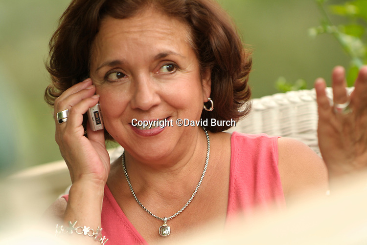 Hispanic woman talking happily on cell phone