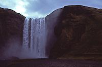 ISLANDA, bellissimo paesaggio naturale: una grande cascata scende da una montagna su un fiume.