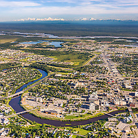 Aerial view of the Chena River winding through the city of Fairbanks and the Tanana River to the south of town, Alaska Range mountains on the distant horizon.