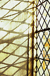 Detail of stone-framed window with diamond-leaded panes of clear or pale yellow glass throwing shadows onto niche wall