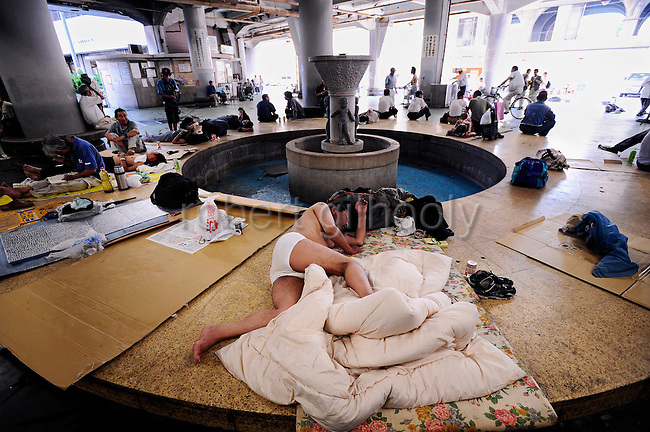 Homeless and jobless men hang around a communal area of the Nishinari Labor Welfare Center in the Kamagasaki district of Osaka, Japan on July 23 2008. Over 1,000 homeless people line up each evening in hope of securing a bed in the several shelters found in Kamagasaki, a slum-like area near the bright lights of Osaka's business center that also is notorious for its  cardboard box dwellings, 6-pound a night basic accommodations and drug trafficking conducted by Japan's mafia, the yakuza. During the summer months, when temperatures inside the non air-conditioned shelters soar, many homeless prefer to take to the outdoors. .Photographer: Robert Gilhooly