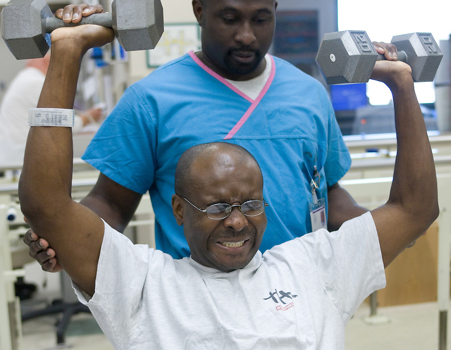 mayoheart 158497-- Charles Okeke works out at the Mayo Clinic Hospital. JoJo Okyere monitors Okeke's  Total Artificial Heart. The Total Artificial Heart weighs 400 pounds keeping him stuck in the hospital until he can get a heart transplant or until he can be hooked up to a more portable version. (Pat Shannahan/ The Arizona Republic)