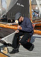 Nederland Spakenburg 2016. Visserijdag in Spakenburg. Tijdens de Visserijdag ligt de haven vol met historische schepen en dragen veel inwoners klederdracht. Man is een visnet aan het breien. Foto Berlinda van Dam / Hollandse Hoogte