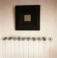 A small mirror with a black surround hangs on the wall above a metal sculptures in the shape of flowers.