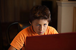 Young boy in orange tee shirt wears headphones while he intently watches a computer game - EXCLUSIVELY AVAILABLE HERE