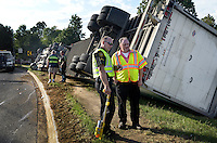 NWA Democrat-Gazette/BEN GOFF @NWABENGOFF<br /> Springdale police officers work the scene of an overturned semi truck on Monday Sept. 14, 2015 on White Road at the intersection with Elm Springs Road in Springdale. Matthew Thomas of Fayetteville was traveling South on White Road and was stopped waiting to make a right turn onto Elm Springs in a Dodge pickup truck. Thomas describes seeing the semi coming around a curve in the road, already beginning to roll as it approached his pickup. The semi clipped Thomas' pickup, causing minor damage, before rolling onto it's right side and sliding off the road.