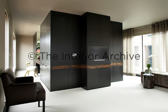 A television is built into a floor to ceiling run of wardrobes in dark wood in a spacious bedroom.