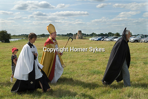 The Bishop of Norwich Rev Graham James arrives at St Benets Abbey. A Brother of St Benets leads the Bishop towards the ruined Abbey, along with the Vicar of Horningm Sandra Ellison.