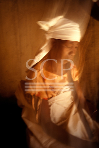 Kilamba, Tanzania. Female traditional healer shaman performing a healing ritual in the house of a sick woman.