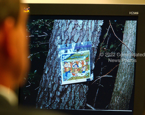 A bag containing a cartoon and a message tacked to a tree outside the Ponderosa Steak House in Ashland, Virginia, shooting site is displayed on a computer screen during the trial of sniper suspect John Allen Muhammad in courtroom 10 at the Virginia Beach Circuit Court in Virginia Beach, Virginia, on October 31, 2003. <br /> Credit: Adrin Snider - Pool via CNP