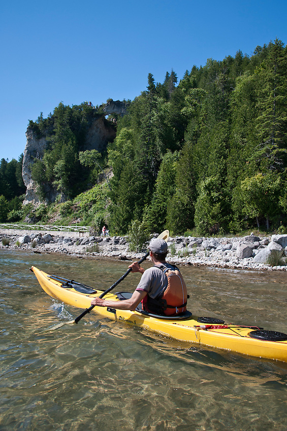 A kayaker explores the shoreline of Mackinac Island Michigan on Lake Huron.