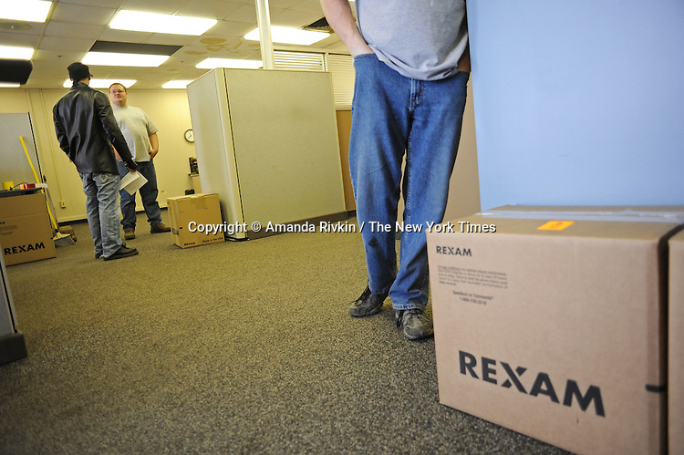 Management employees clean out the largely boxed up front office of the Rexam plastic bottle cap plant that shuttered this fall in Constantine, Michigan on December 22, 2010.