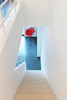 An elevated view looking down a minimalist staircase to the floor below where a red Eames chair provides a vibrant spot of colour against the white background.