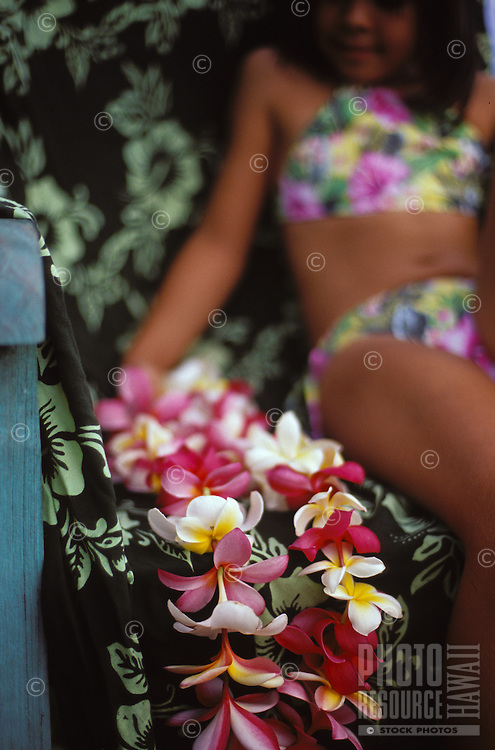 Plumeria leis of red, white, and pink flowers, with young girl in background. Waialua, Hawaii.