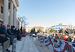 Mineola, New York, USA. January 1, 2018. At podium, Nassau County Executive LAURA CURRAN, who has just be sworn in as the County's first female Executive, delivers her Inaugural Adress during the outdoor ceremony held in front of Theodore Roosevelt Executive & Legislative Building. Nassau County Legislators are sitting on chairs left of the podium. Temperature was a freezing 14 ℉ Fahrenheit / -10 ℃  Celsius, and people in audience stood close together on and near the vast entrance stairs steps.