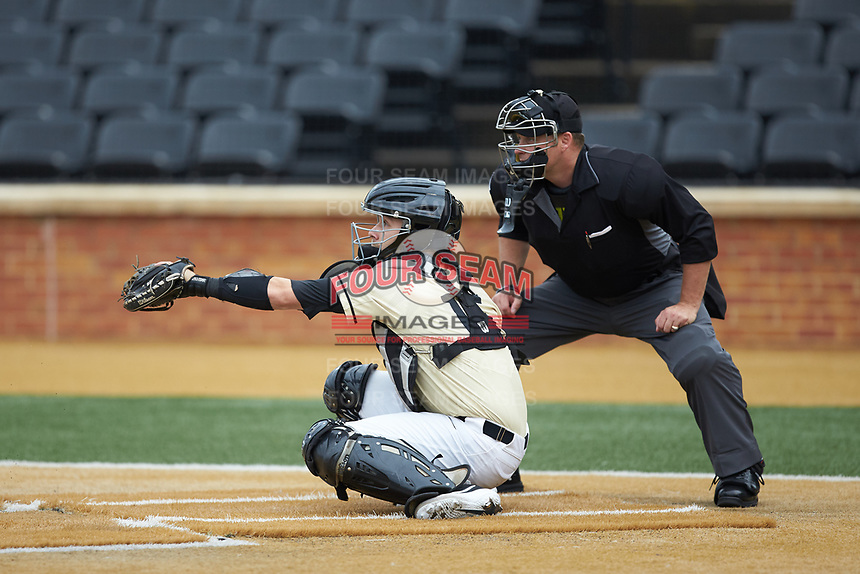 Wake Forest Demon Deacons catcher Logan Harvey (15) sets a target as home plate umpire Jonathan Merry looks on during the game against the Miami Hurricanes at David F. Couch Ballpark on May 11, 2019 in  Winston-Salem, North Carolina. The Hurricanes defeated the Demon Deacons 8-4. (Brian Westerholt/Four Seam Images)