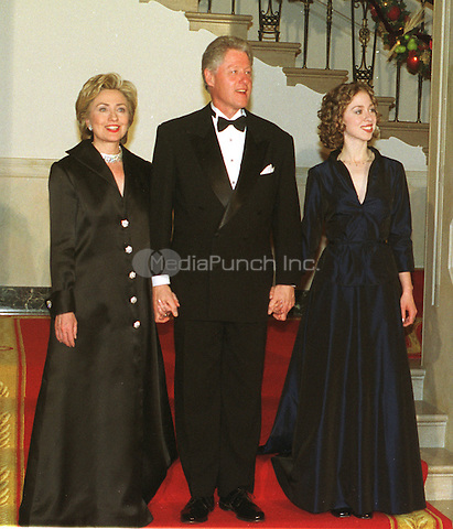 The First Family descends the Grand Staircase to meet their guests at the White House Millennium dinner in Washington, D.C. on December 31, 1999. (L-R) First Lady Hillary Rodham Clinton, United States President Bill Clinton, Chelsea Clinton..Credit: Ron Sachs / CNP/MediaPunch.