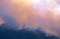 870000349 a los angeles county fire fighting helicopter flying through thick smoke performs aerial retardant drop on homes directly in the burn path of the topanga fire in the hills above the san fernando valley in southern california