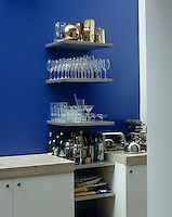 Cantilevered stainless steel shelves slotted between a pair of kitchen units house a collection of glassware and bottles