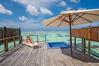 Maldives, Rangali Island. Conrad Hilton Resort. Woman relaxing in lounge chair in view of the ocean and the back deck of the water villa.