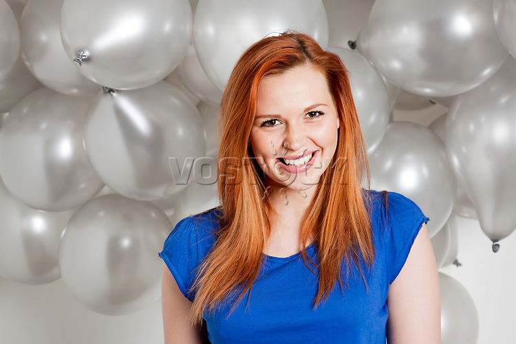 Happy young woman in front of balloons<br />