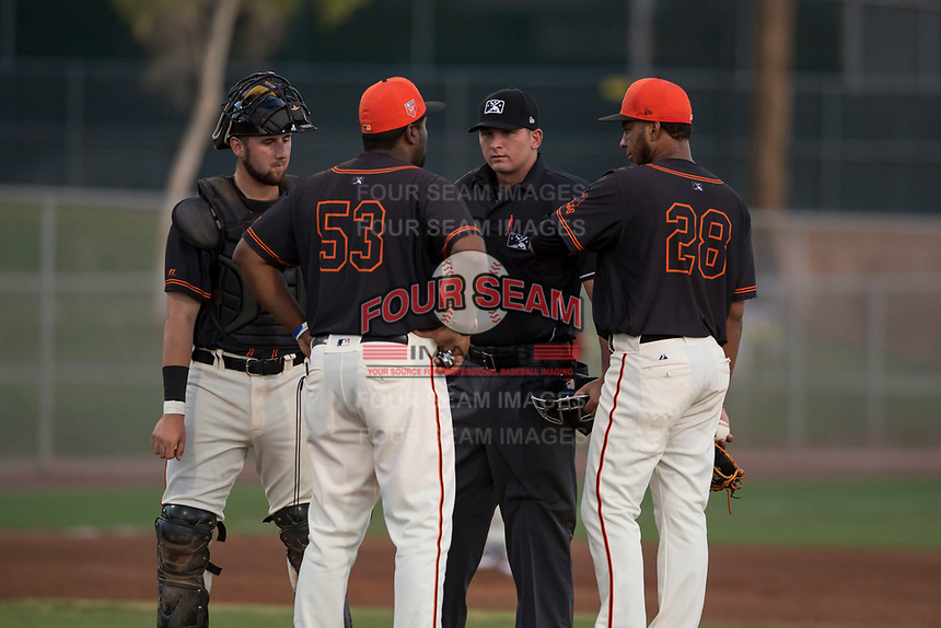 Home plate umpire Kevin Levine breaks up a meeting on the mound between Cody Brickhouse (6), Mario Rodriguez (53), and Luis Moreno (28) during an Arizona League game between the AZL Giants Black and the AZL Athletics at the San Francisco Giants Training Complex on June 19, 2018 in Scottsdale, Arizona. AZL Athletics defeated AZL Giants Black 8-3. (Zachary Lucy/Four Seam Images)