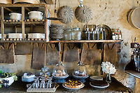 Homemade cakes displayed on a wooden table under a rudimentary shelving unit in the kitchen