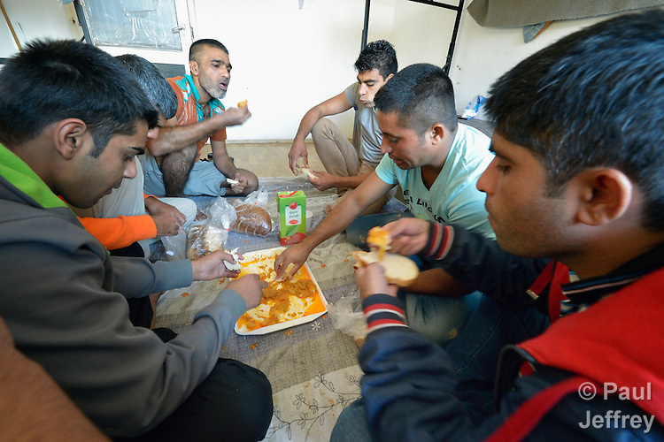 Migrants from Pakistan eat a shared meal in a government-run refugee center in Vamosszabadi, Hungary. Hungarian Interchurch Aid, a member of the ACT Alliance, provides child care and other services to residents in the center, who come from Syria, Iraq and other countries and are bound for western Europe.