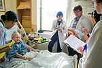 Hospitalist Poonam Sharma, MD, center, leads interprofessional rounds with charge nurse Faith Gibson, RN, left, social worker Allen Gibson, pharmacist Hannah Pippin, and physician assistant student Joshua Davidoff during interprofessional rounds in the cardiac telemetry unit with patient Gloria Bledsoe, 89, at Duke Regional Hospital.