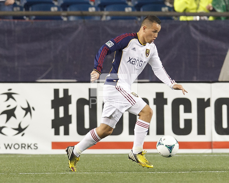 Real Salt Lake midfielder Luis Gil (21) brings the ball forward.  In a Major League Soccer (MLS) match, Real Salt Lake (white)defeated the New England Revolution (blue), 2-1, at Gillette Stadium on May 8, 2013.