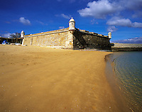 Golden sand on the beach at Lagos, with the old harbour defenses, the 17th century Forte Bandeira, under a deep blue sky, Algarve, Portuga
