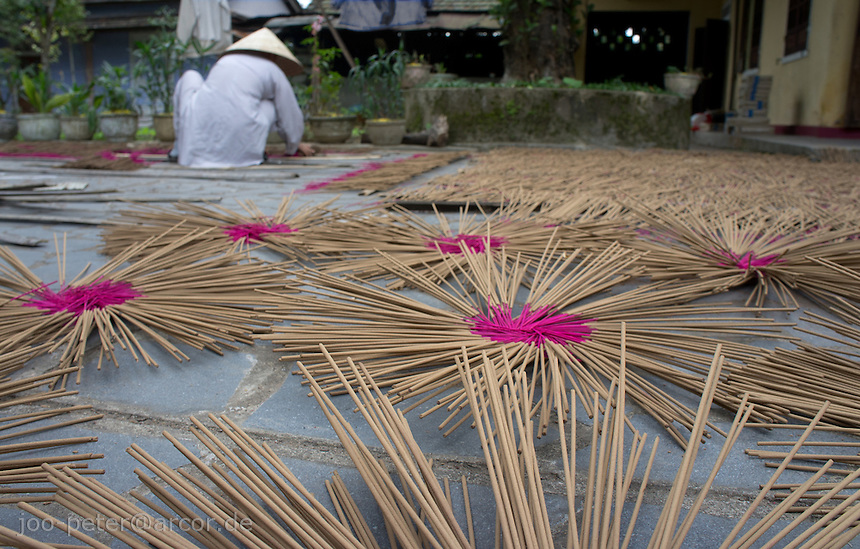 monk with grey robe and traditional vietnamese leaf hat collects newly produced incest sticks which dried in the sun in the courtyard oof his monastry, outside city Hue, Vietnam