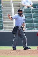 Home plate umpire Derek Gonzales makes a strike call during the South Atlantic League game between the Hagerstown Suns and the Kannapolis Intimidators at CMC-Northeast Stadium on June 1, 2014 in Kannapolis, North Carolina.  The Intimidators defeated the Suns 5-1 in game one of a double-header.  (Brian Westerholt/Four Seam Images)