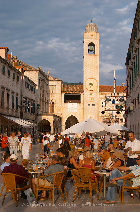 The main street Stradun Placa with traditional houses and flocks of tourists, view over clock tower and loggia Luza on the central square in evening sunlight Dubrovnik, old city. Dalmatian Coast, Croatia, Europe.