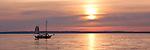 Washington, Bellingham. A single ship sails across a pink sunset over Bellingahm Bay.