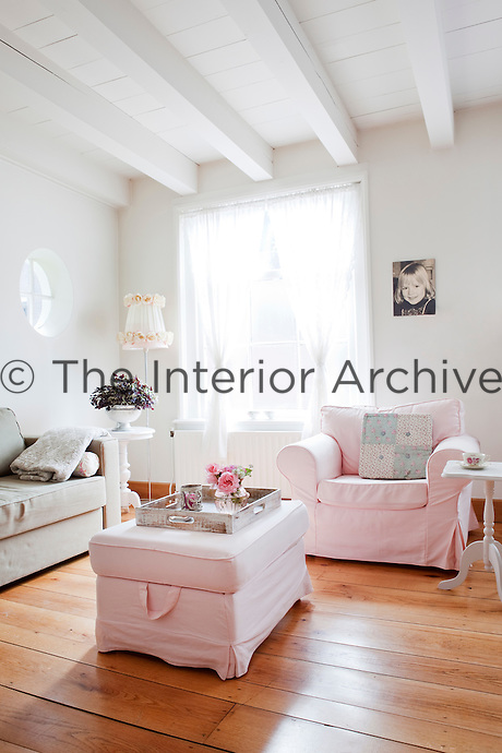 Pale pink loose covers on the armchair and ottoman add a subtle hint of colour to the spacious white living room