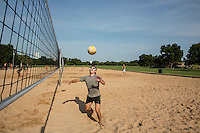 Fit man playing volleyball sets up the ball under a clear blue sky on the sand volleyball courts at Zilker Park.