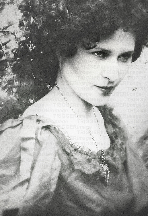 A monochromatic image of a woman in a victorian outfit and a large pendant on her necklace, with long dark curly hair and a wicked or angry facial expresion.