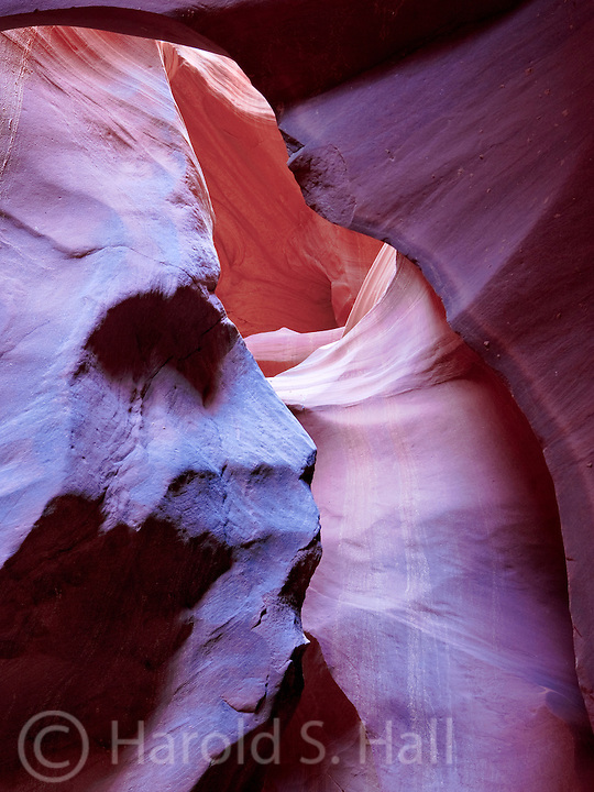 Antelope Canyon near Page Arizona is a slot canyon.  Near the top, where the sun is brightest, the colors are bright yellow.  Closer to the bottom of the canyon the colors are orange and blue in the darkest areas.  In this photo the sandstone appears to be the face of an Indian chief.