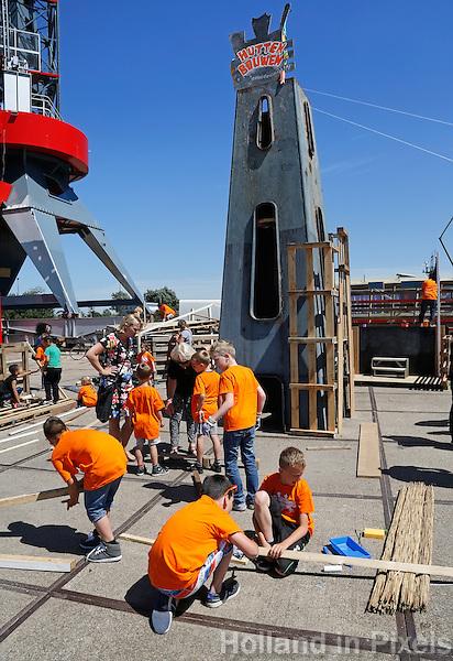 Landelijke buitenspeeldag. Kinderen spelen buiten op de NDSM werf in Amsterdam. Hutten bouwen