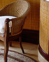A wicker chair in the corner of an ensuite bathroom decorated with wicker wall panelling
