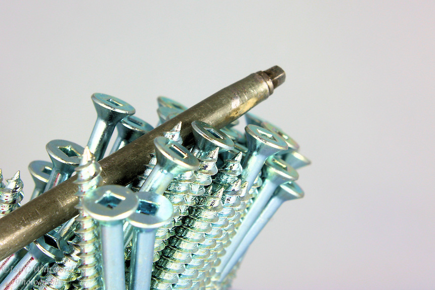 A group of Robertson head screws with the blade of the used screwdriver