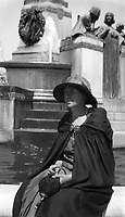 Woman in cape and umbrella seated in front of a fountain, circa 1930's.   (photo: www.bcpix.com)