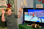 Wantagh, New York, USA. February 7, 2016. Volunteer MIKE DAY, 13, of Wantagh, looks as if he's giving coaching advice to the gray kitten player with the red collar on TV in Hallmark Channel Kitten Bowl III. At Last Hope Animal Rescue's Open House, the guests cheer on their team, the Last Hope Lions, which the tiny tabby szs a member of. Over 100 adoptable kittens from Last Hope Inc and North Shore Animal League of America participated in the pretaped games, and the Home and Family Felines won the 2016 championship, which first aired the day of Super Bowl 50.