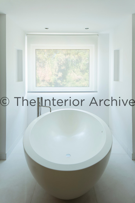 The minimalist bathroom features white walls and flooring and a sleek, oval shaped free-standing bath tub.