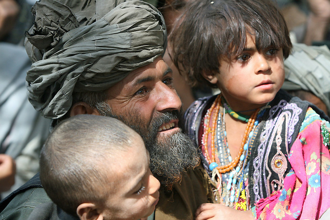 A man from the nomadic Kuchi tribe and two children wait outside the district center of Shar-e-Safa in Zabul province, Afghanistan. U.S. troops provided medical care, and Afghan police distributed winter clothes, food staples and other relief items to about 200 people before they ran out of supplies.  Aug. 25, 2008. DREW BROWN/STARS AND STRIPES