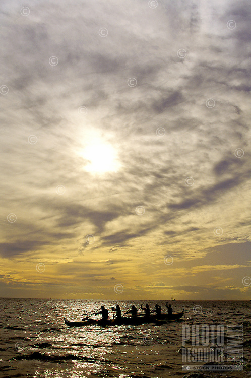 Paddling an outrigger canoe off Waikiki in late afternoon, with sun almost setting.