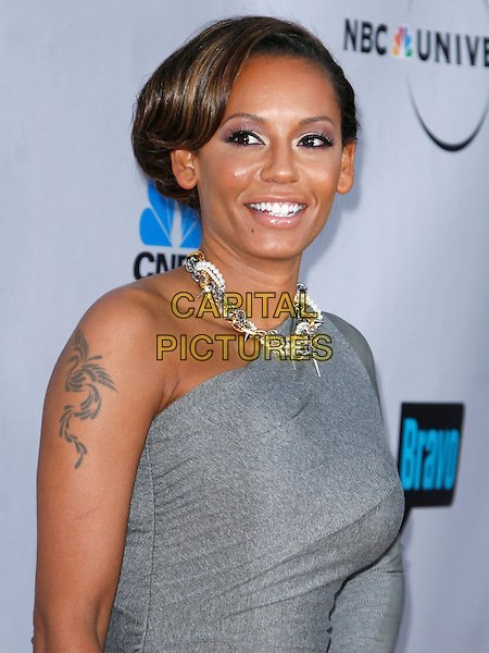 MELANIE BROWN (MEL B). arriving at the The Cable Show 2010 To Feature An Evening With NBC Universal held at  Universal Studios Hollywood in Universal City, California, USA, .May 12th, 2010..portrait headshot tattoo necklace grey gray one shoulder sleeve hair up  smiling chains .CAP/ROT/AMB.©Adriana M. Barraza /Roth Stock/Capital Pictures