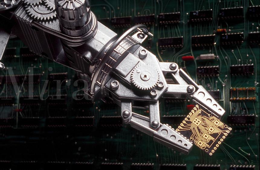 Robotic arm holding a mini circuit board.